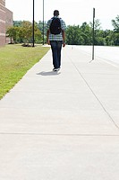Male high school student walking along pavement