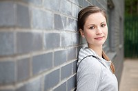 Young woman by wall (thumbnail)