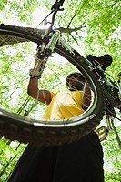 Male cyclist carrying bike in forest
