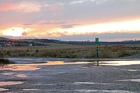 Coastal carpark with emergency telephone and puddles at sunset, Salthouse Beach, Norfolk, England, february