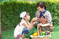 Mother and daughter holding basket filled with fresh vegetables