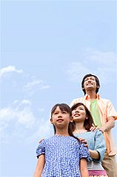 Family looking up at sky, smiling, copy space