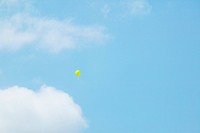A single yellow balloon floating in the sky