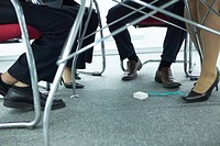 Legs of business colleagues under a meeting table