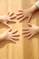 Two children´s hands on wooden floorboards