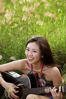 smiling woman playing guitar on grass