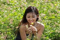 young woman looking at flower in grassy field