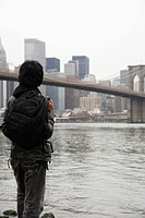 young man wearing a back pack while looking at the city skyline and bridge