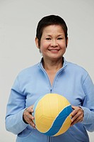 Mature Chinese woman holding a volleyball