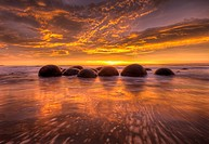 Moeraki boulders at dawn as SW front passes overhead, near Oamaru, Otago,