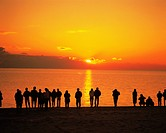 People watching the sun rise from a beach in Tsu, Mie Prefecture, Japan