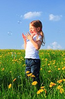girl playing with bubbles in field of Dandelions, Zuercher Oberland, Zuerich, Switzerland