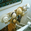 Aerial view of straw hats on pegboard above white staircase
