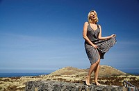 Hawaii, Big Island, Kohala Coast, Woman in a beautiful dress dancing in a desolate field.