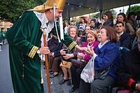 Penitent giving candy Palm Sunday processionCofradia del Santisimo Cristo de la Esperanza Holy Week  Murcia  Spain