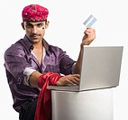 Portrait of an actor portraying a tapori holding a credit card and using a laptop