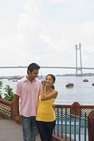 Couple smiling at each other with a bridge in the background, Vidyasagar Setu, Hooghly River, Kolkata, West Bengal, India