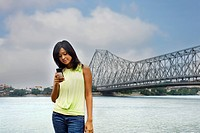Woman text messaging on a mobile phone with a bridge in the background, Howrah Bridge, Hooghly River, Kolkata, West Bengal, India
