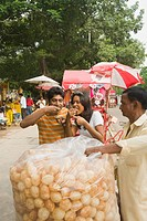 Vendor serving Indian snack panipuri to a couple on a street, Kolkata, West Bengal, India