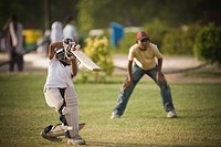 Boys playing cricket in a playground, New Delhi, India