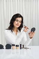 Woman applying make_up on her face