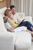 Family of three sit reading a digital book