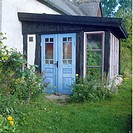 Blue double doors on porch extension on country cottage