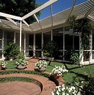 Architectural trellis over circular patio with containers of white flowers