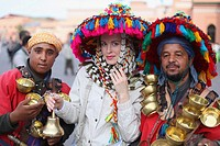 Blonde woman with water sellers in Jemaa El Fna Square in Marrakech, Morroco