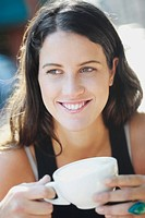 Close_up of a young woman holding a cup and smiling