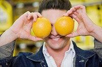 Close_up of a young man covering his eyes with two oranges