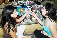 Side profile of two young women choosing a necklace