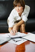 Portrait of a businesswoman signing documents on the table