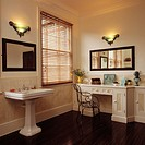 Art Deco_style wall lights and slatted wooden blind in traditional bathroom with mirrors and large pedestal basin