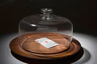 Close_up of a glass container covering a playing card on a dish
