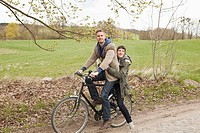 A man giving a ride to his girlfriend on a bicycle in the country