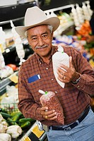 Portrait of a senior man holding packets in a supermarket