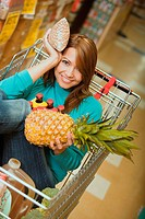 Portrait of a young woman sitting in shopping cart and holding a pineapple and a packet
