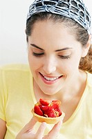 Close_up of a young woman looking at a strawberry tart