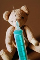 Close_up of a syringe in front of a teddy bear