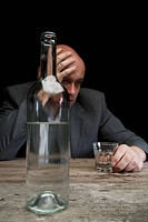 A drunk and depressed businessman holding a glass of vodka
