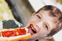 Portrait of a boy eating a hot dog