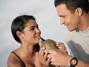 Close_up of a young woman drinking coconut water from a coconut held by a young man