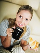 Portrait of a young woman holding a coffee cup and a croissant