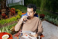 High angle view of a mid adult man sitting and drinking wine