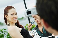 Two young men taking a picture of a young woman applying make_up