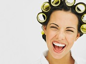 Close_up of a young woman with curlers in her hair laughing