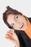 Close_up of a businesswoman adjusting her eyeglasses and looking up