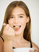 Portrait of a teenage girl eating cornflakes with a spoon