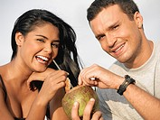 Portrait of a young couple holding a coconut